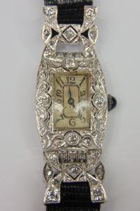 Orologio da sera decò, in oro bianco con diamanti taglio brillante e rosette,con movimento di forma marcato
