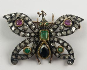 Gold and silver butterfly shaped diamond brooch with diamonds, emeralds, rubies and sapphire. Early 20th century