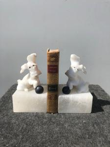 Pair of alabaster bookends depicting dogs with ball.