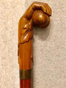Stick (erotisch) mit Knopf aus Buchsbaum, der eine Hand mit Früchten darstellt.