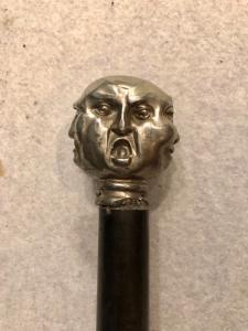 Stick with metal knob depicting 4 grotesque faces. Ebony horn.