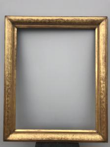 Gran marco en madera tallada y pan de oro con motivos florales.