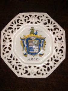 Piatto tagliere ottagonale in maiolica con traforo e stemma nobiliare.Pavia.