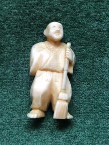 Netsuke 'em marfim com personagem e vassoura Japão.