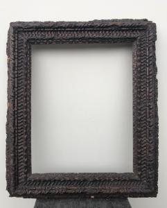 Wooden frame carved with geometric motifs.