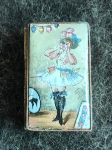 Caixa de fósforos em metal e esmalte representando uma donzela provocante.