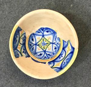 Ciotola in maiolica a decoro geometrico,frammentata e ricomposta con restauro archeologico.Faenza