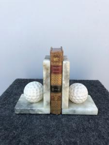 Pair of alabaster bookends depicting golf balls.