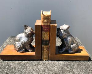 Pair of metal and wood bookends depicting dog and cat.