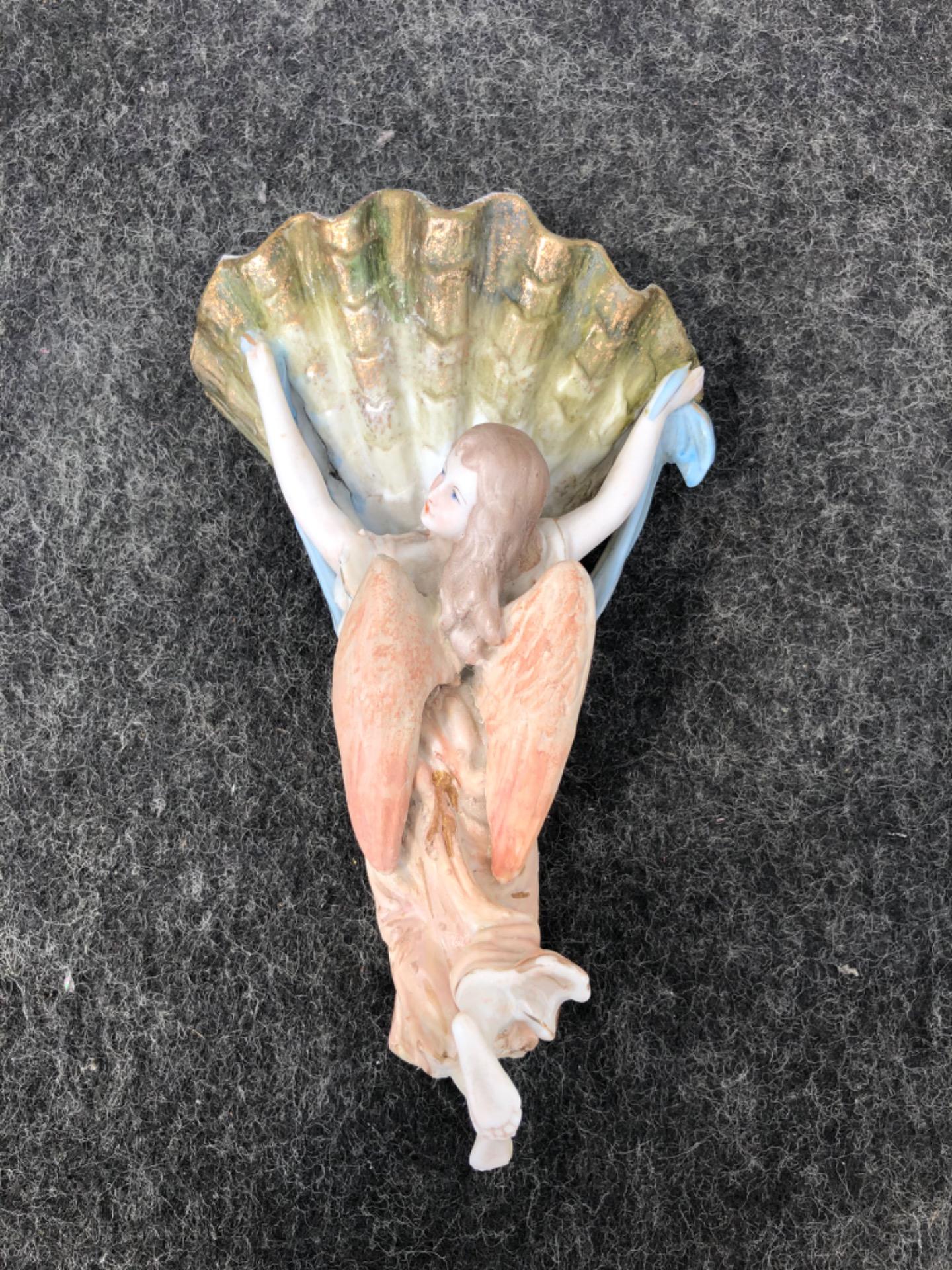 Acquasantiera in porcellana bisquit raffigurante angelo di spalle che regge la coppa a conchiglia.Italia.