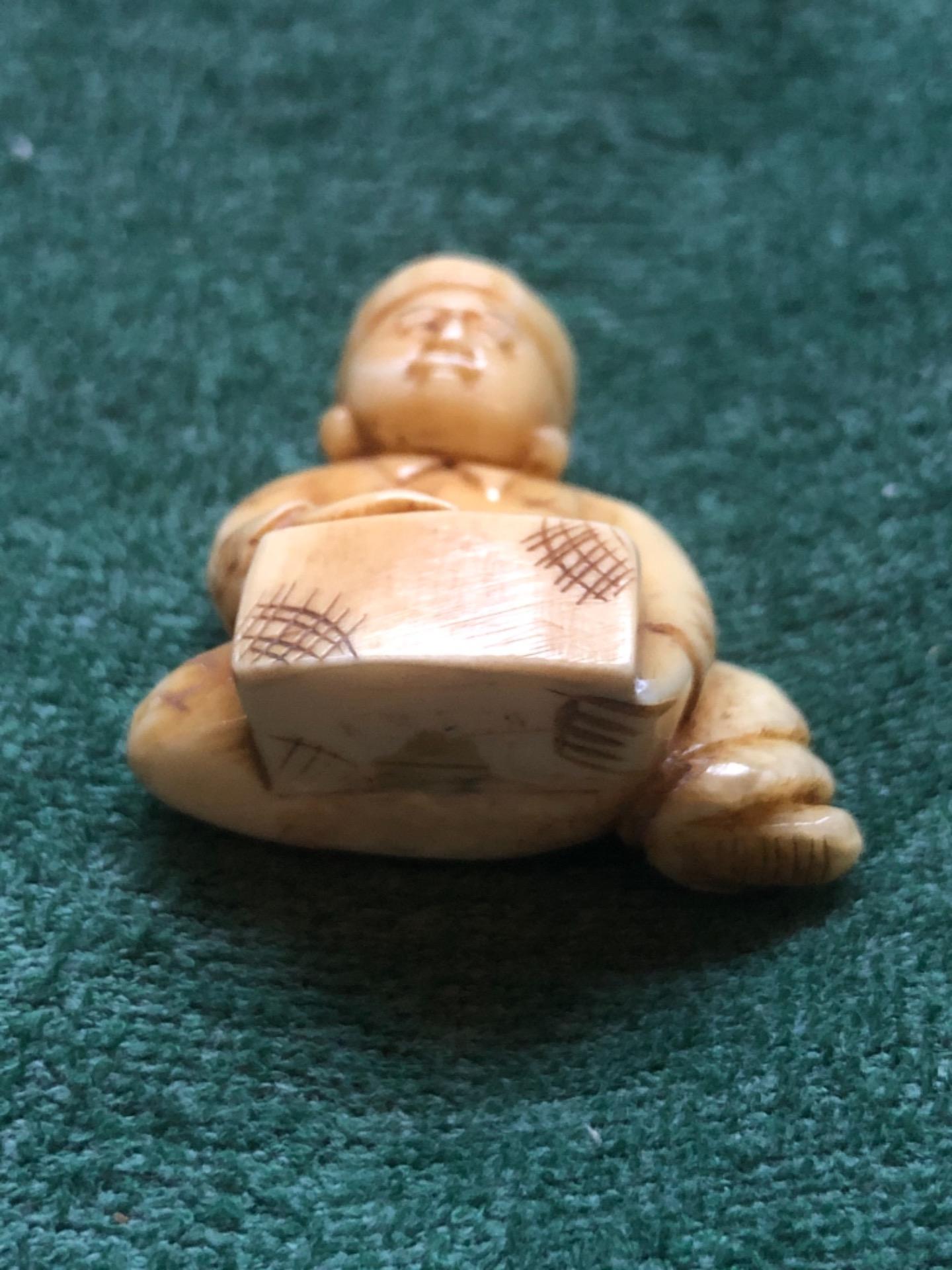 thumb5|Netsuke' in avorio con personaggio seduto con ceppo di legno.Giappone.
