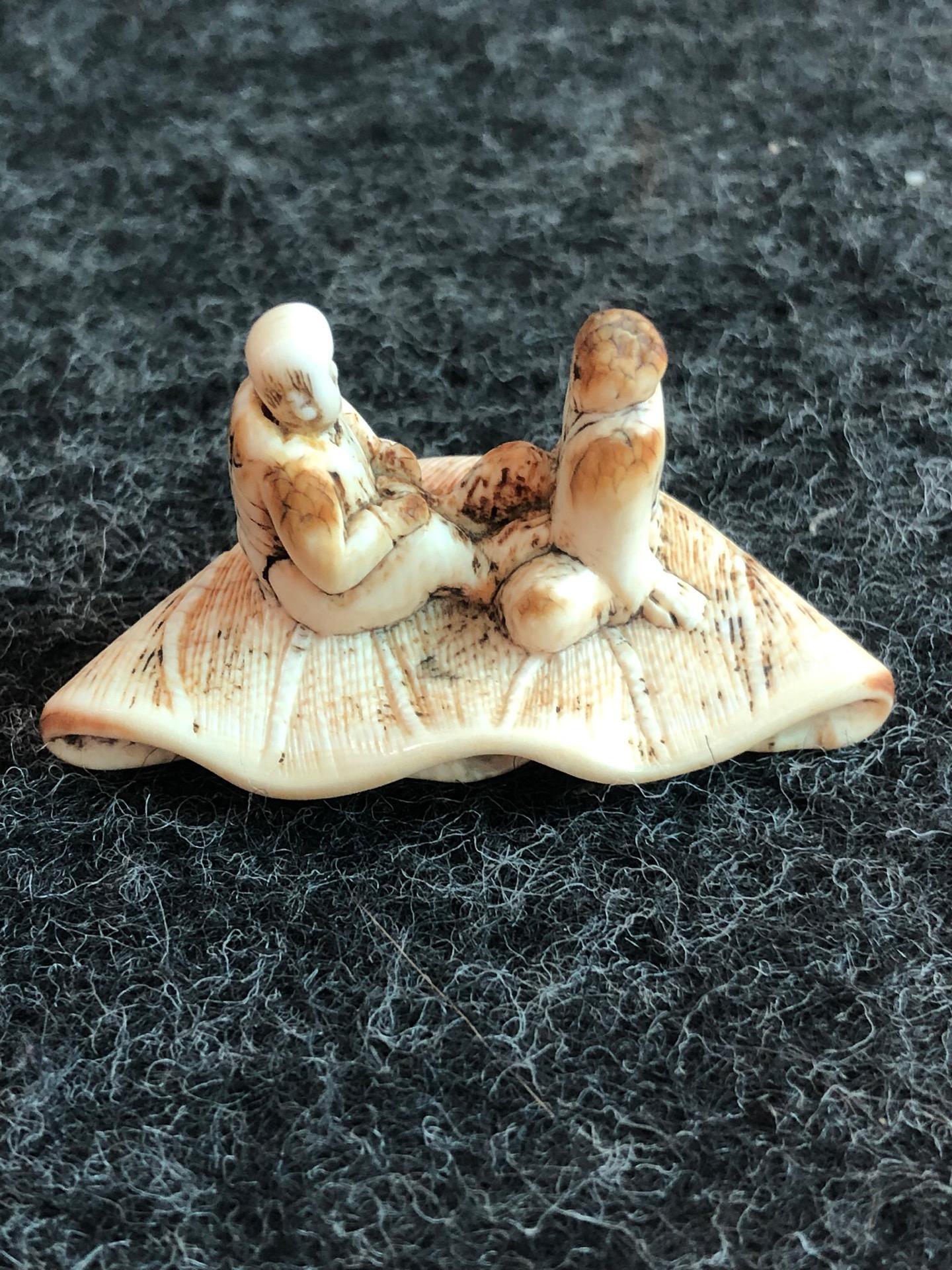 Netsuke' in avorio raffigurante due personaggi seduti su foglia di loto.Giappone