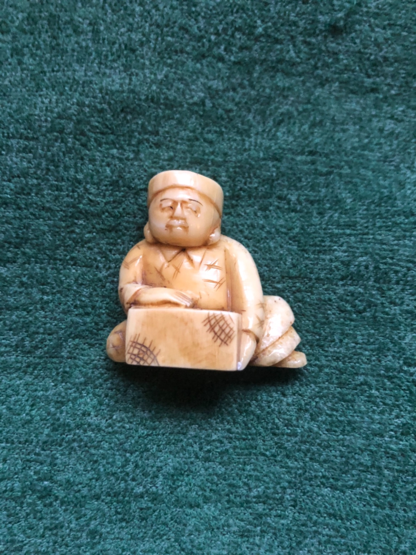 Netsuke' in avorio con personaggio seduto con ceppo di legno.Giappone.