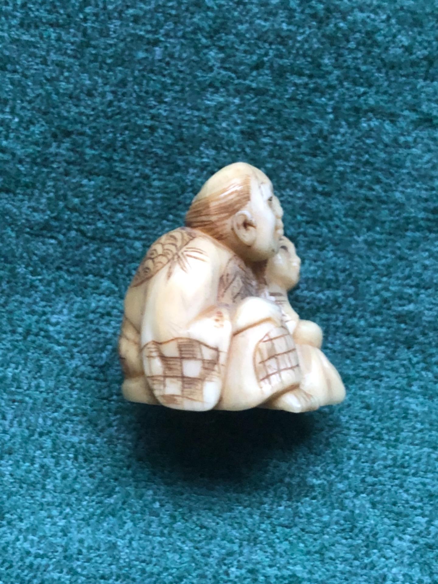 thumb4 Netsuke' in avorio con personaggio seduto e bambino con rana in testa.Giappone.