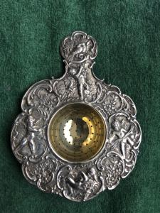 Colino da te' in argento con 4 putti,uccellini,motivi floreali e rocaille.