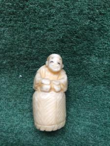 Ivory netsuke 'com personagem sentado em uma cesta de vime.