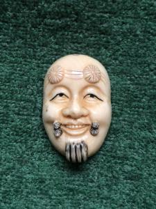 Netsuke'在与男性面孔的象牙中。