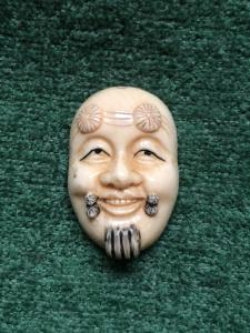 Netsuke 'em marfim com rosto masculino. Japão.