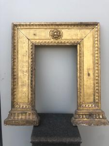 Marco soporte en madera tallada y dorada con motivos geométricos.