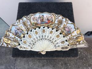 Ventaglio in avorio traforato e dorato con Pavese in carta con stampe acquarellate con scene galanti e campestri.Francia.