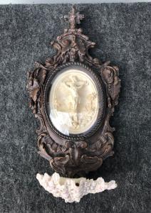 Acquasantiera in legno,pastiglia e coppa in porcellana a conchiglia.Ovale in schiuma di mare raffigurante crocifissione.Francia.
