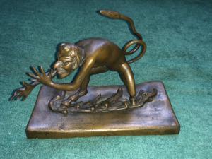 Escultura de bronze representando um diabo fazendo framboesa. Áustria.