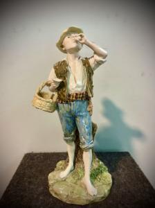 Escultura policromada em faiança representando um fazendeiro bebendo ovos. Iniciais do autor na base. Fabricação de Ginori.