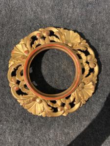 Cornice tonda in legno intagliato e dorato con motivi vegetali e conchiglie.