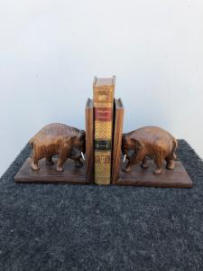 Pair of rosewood bookends depicting elephants with ivory tusks.