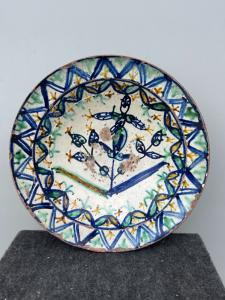 Керамическая тарелка из ангоба с `` популярным '' декором со стилизованными растительными элементами.