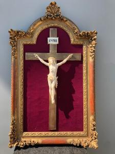 Cristo in avorio con cornice dorata in legno intagliato.