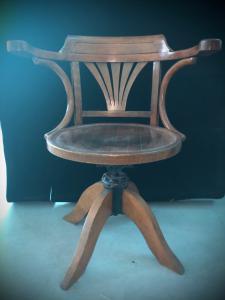 Sedia in legno chiaro regolabile in altezza.