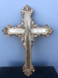 Cruz en madera tallada y dorada con estilizados motivos vegetales.