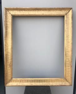 Frame in carved wood and gold leaf with engraved geometric motifs.