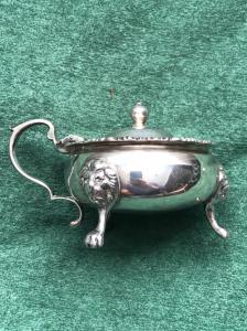 Salsiera in argento  a tre piedi con mascheroni e zigrinature.Londra 1933.