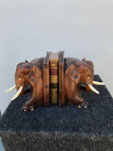 Pair of teak wood bookends depicting a pair of elephants. Ivory tusks.