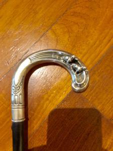 Bastone con impugnatura in argento traforato con due cani bassotti in rilievo.
