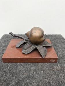 Tintero de bronce en forma de pera sobre base de mármol.