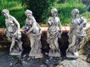 4 concrete garden statues depicting the 4 seasons