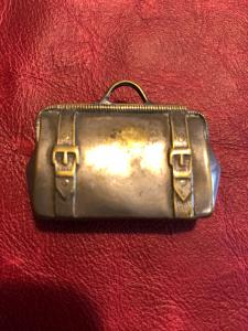 Metal matchbox in the shape of a briefcase.