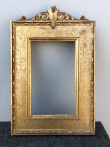 Cornice in legno intagliato e foglia oro con incisioni a motivi vegetali e geometrici e scudo rocaille superiore.