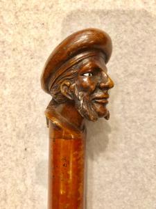 Stick mit Holzknauf, der eine männliche Figur mit Koteletten und Hut darstellt.