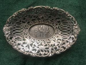 Ovales Herzstück aus versilbertem und perforiertem Metall mit zentraler Szene mit Figuren. Holland.